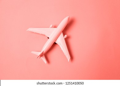 Simply flat lay design miniature toy model plane colored in trendy color of year 2019 Living Coral background. Bright Macro color 16-1546. Travel by plane vacation adventure trip journey tour concept