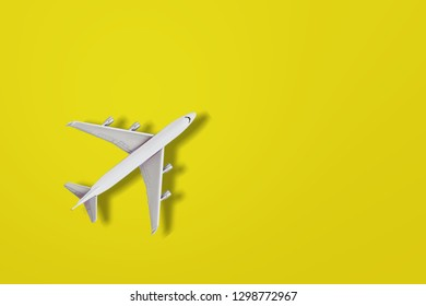 Simply flat lay design miniature toy model plane on yellow colorful paper trendy background. Travel by plane vacation summer weekend sea adventure trip journey ticket tour concept          - Image