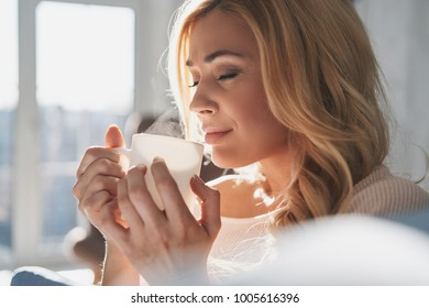 Simply happy. Attractive young woman holding a cup and keeping eyes closed with smile while spending time at home