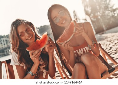 Simply having fun. Two attractive young women smiling and eating watermelon while sitting on the beach