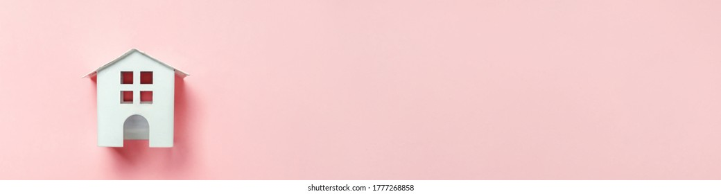 Simply minimal design with miniature white toy house isolated on pink pastel colourful background. Mortgage property insurance dream home concept. Flat lay top view copy space banner