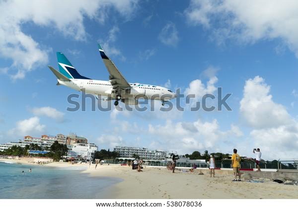 Simpson bay, Sint Maarten-December 12, 2016: West Jet airplane landing on Princess Juliana International airport, low beach landing.