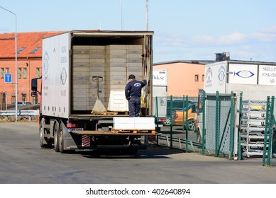 Simrishamn, Sweden - April 1, 2016: Male truck driver loading fish crates into the back of the truck outside a fish industry.