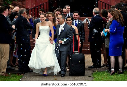 Simsbury, Connecticut - September 21, 2014: Bride and groom are showered with bubbles as they emerge from church following their wedding ceremony