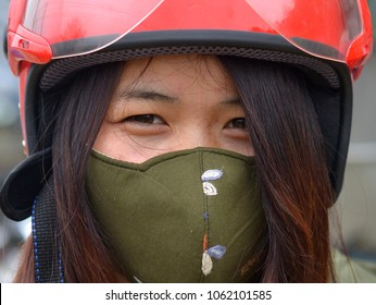 SIN CHENG, LAO CAI/VIETNAM - March 21, 2018: Vietnamese scooter girl wears a red motorcycle crash helmet and covers her face with a green protective anti fog and haze face mask; on March 21, 2018.