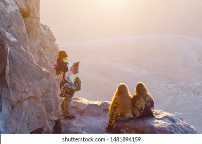 Sinai Peninsula, Egypt, May 9, 2019. Girls greet dawn and take pictures on Mount Moses, Sinai Peninsula, Egypt