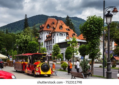 SINAIA, ROMANIA - JUNE 28, 2017: The main street of Sinaia Bulevardul Carol with people on it. There is the sightseeing train opposite the Rina Cerbul Hotel. Sinaia is a famous resort in Romania.