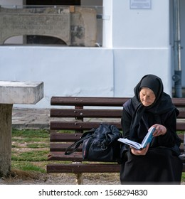 Sinaia, Romania - November 16, 2019: elderly religious woman practicing orthodox Catholic Christianity, sitting on a bench in front of the Old Church of the Sinaia monastery, while reading a book.