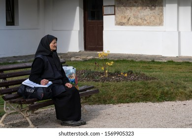 Sinaia, Romania - November 16, 2019: elderly religious woman practicing orthodox Catholic Christianity, sitting on a bench in front of the Old Church of the Sinaia monastery