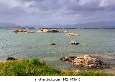 Sinas rocki islets on the sea in Vilanova de Arousa with stormy clouds