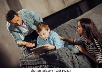 Sincere concern. Loving young parents being around their pre-teen son playing on the tablet and trying to make him stop while the boy being reluctant