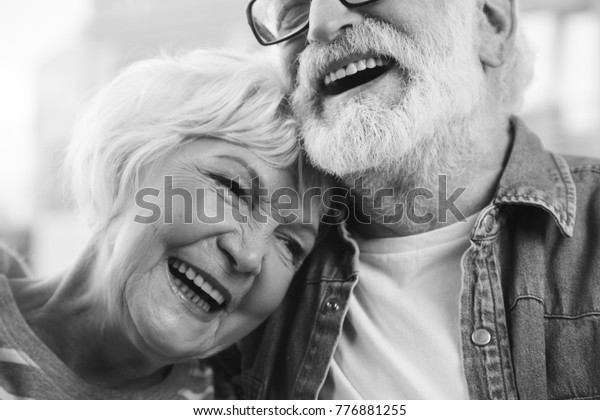 Sincere emotions. Close up black-and-white portrait of mature married man and woman bonding to each other while laughing. Happy retirement concept