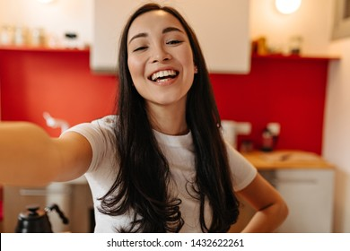 Sincere girl in white T-shirt laughs, looks into camera and takes selfie in kitchen