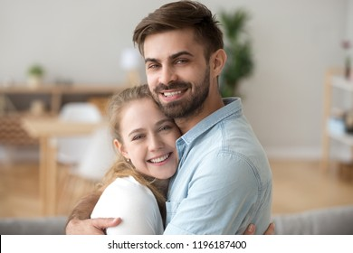 Sincere just a married couple in love hugging. Head shot portrait husband and wife embracing spend free time together at home on weekend looking at camera. Romantic relationships and dating concept