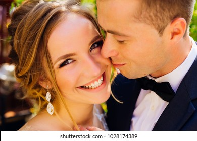 sincere smile of a beautiful bride looking at camera while groom touches her softly