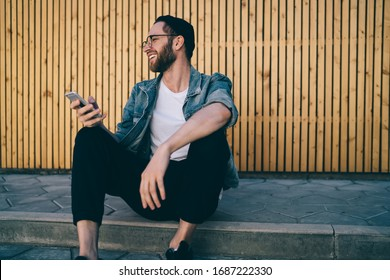 Sincerely Caucasian man dressed in trendy streetwear apparel enjoying communication networking via cellphone device using 4g wireless connection in city, joyful hipster guy blogging website via app