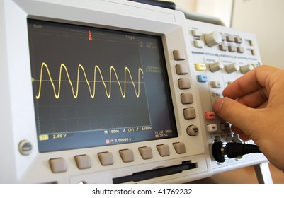 sine wave on oscilloscope screen and engineer's hand calibrating the instrument