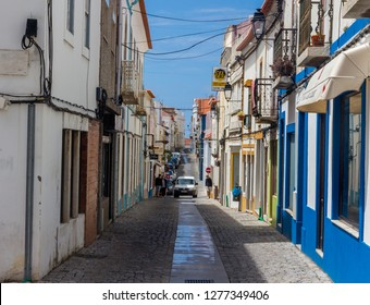 Sines, Portugal - May 5, 2017: Narrow, picturesque cobbled stone street in the town of Sines, Portugal.