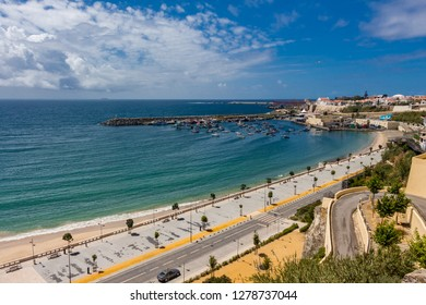 Sines, Portugal - May 5, 2017: Panorama view over Vasco da Gama beach and town of Sines. Turquoise water. Moody sky, clouds.