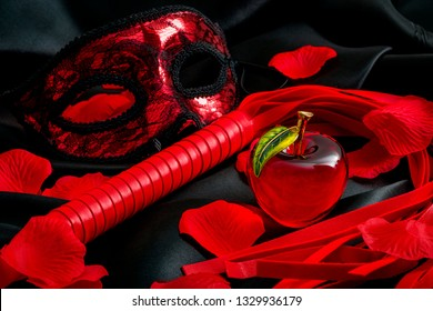 Sinful adult sex games, kinky romance and BDSM play concept theme with a bondage lace mask, red whip or flogger, rose petals and a glass apple representing sin on black silk background