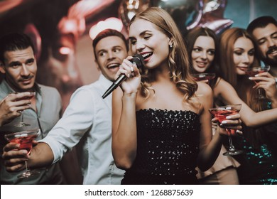 Sing and Drink. Black Dress. Trendy Nightclub. Have Fun. Background. Cheerful. Smiling Girl. Singing Songs. Handsome Men. Beautiful Girls. Friends at Karaoke Club. Karaoke Club. Celebration.