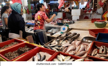 Singapore- 01 Mar, 2020: Customers buy fresh fish from a stall in a wet market in Singapore. The traditional Asian wet market still exist in this modern city.