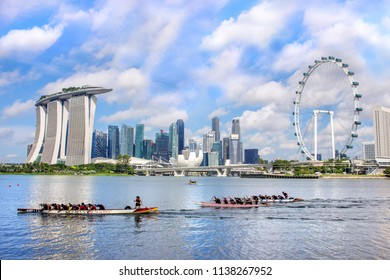 Singapore 11 Aug 2017 - Skyline of the city financial district with Marina Bay Sands hotel and Singapore Flyer, where people practicing dragon boat kayaking for independence day celebration