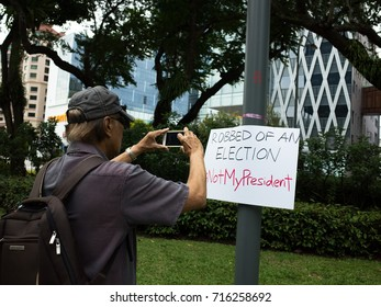 SINGAPORE, 16 SEPTEMBER 2017: A protester takes a photo of a protest sign at the sit-in protest at Speaker's Corner, Hong Lim Park