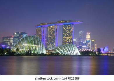 Singapore, Singapore - 17 January 2020 : Aerial view of Singapore Gardens by the Bay botanical gardens and Marina bay sands at twilight.