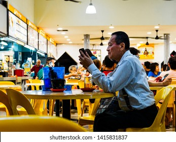 SINGAPORE - 17 MAR 2019 - A middle aged man in office attire enjoys a late night beer at an eatery / coffeeshop / kopitiam, / hawker centre in Singapore