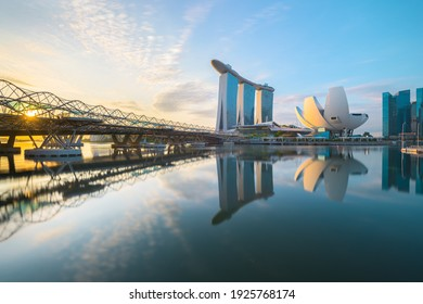 Singapore - 19 Dec 2019: A composite view of the Helix Bridge, the Sands Resort hotel and the ArtScience Museum reflecting on the Marina Bay reservoir at sunrise, in Singapore