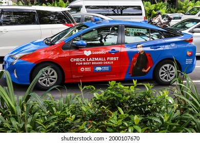SINGAPORE - 2 JUN 2021: A Comfortdelgro taxi's car wrapping advertisements of e-commerce platform LAZADA generate revenue for the taxi company. The car is a mobile electronic ad billboard for Lazada