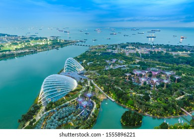 Singapore, Singapore - 25 September 2019: Singapore Gardens by the Bay botanical gardens aerial view and Marina Barrage dam with ship tankers in open sea.
