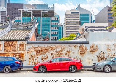 singapore - 25.01.2019: red car on parking next to temple wall with graffiti, with skyscrapers on background