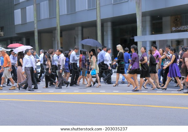 SINGAPORE - 27 May, 2014:Unidentified business people cross road in downtown Singapore. Singapore plays important role as an economic, financial and business centre of South East Asia.