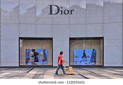 SINGAPORE, 28.08.2017. Orchard shopping mall on Orchard Road in Singapore modern district. worker passes with packages to be delivered in front of the shop facade of famous franch  brand Dior