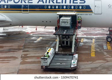 Singapore - 29 June 2019: A ULD loader lifting a unit load device (ULD) from apron dollies to an aircraft's cargo bay of a Singapore Airlines machine at the Singapore International Airport