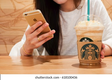 Singapore - 4 March,2017 : close up soft focus woman hand  smartphone with Starbuck caramel macchiato coffee concept.