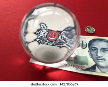Singapore $50 banknote seen through a crystal ball, isolated on a red background with a 10c coin. Banking and Finance, creative photography. Majulah Singapura is Malay for Advance Singapore