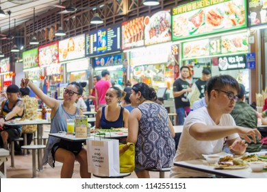 Singapore - 7 July, 2017: Friends from multi racial and culture gathered at Newton Food Center, having fun with foods and busy taking selfie