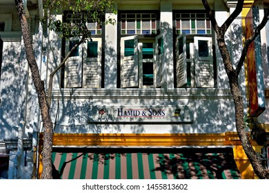 Singapore - 8 July 2019: Old windows with antique white  wooden shutters on a Singapore shop house framed by dark shadows of trees in soft morning light in historic Joo Chiat, Singapore.