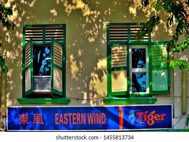 Singapore - 8 July 2019: Old windows with antique green wooden shutters on a Singapore shop house framed by dark shadows of trees in soft morning light in historic Joo Chiat, Singapore.