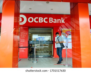 SINGAPORE – 9 APR 2020 – Man wearing face mask outside the entrance of an OCBC Bank branch. The OCBC logo is clearly visible.