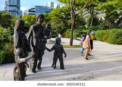 SINGAPORE- 9 AUG 2021: A mother and two daughters walk pass The Happy Family of Five statue standing in the Esplanade's Forecourt Garden. They bond over an outing to de-stress amid Covid-19 curbs.
