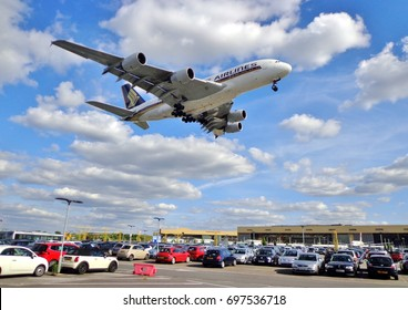"""A Singapore Airlines Airbus A380 """"Superjumbo"""" flies over a car park moments before touching down on Runway 27R at London Heathrow  Airport on July 5, 2016 ."""