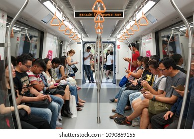 Singapore - APR 21, 2018: Passengers using mobile device in Mass Rapid Transit (MRT) subway train Singapore.