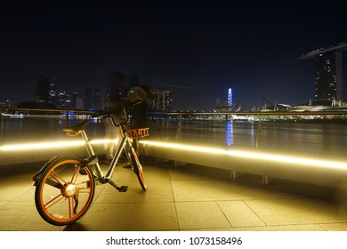 Singapore - April 1, 2018: A bicycle operated by oBike parked near the Merlion Park with view of the Marina Bay Sands and Singapore cityscape. oBike is Singaporean stationless bicycle sharing system.