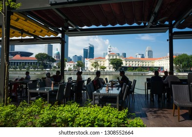 Singapore, Singapore - April 11, 2017: People seated and eating outdoors along the river at Calrke Quay, a famous tourist district in the city.