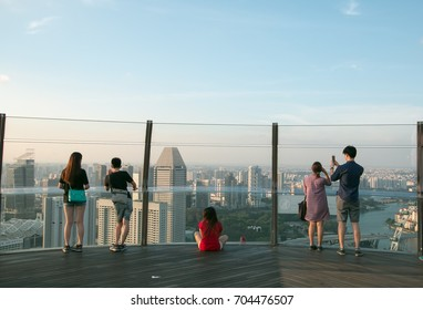 Singapore, Singapore - APRIL 13, 2015 : Tourists are looking at the scenery And take a photo of Singapore City from sands skypark on rooftop of Marina bay sands, on April 13, 2015 in Singapore.