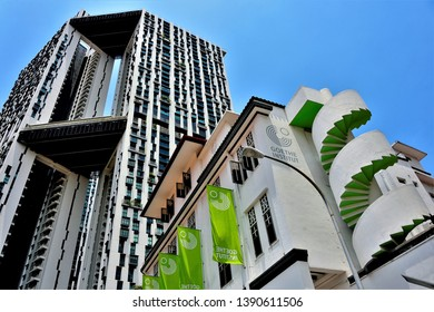 Singapore - April 16 2019: Goethe Institute building with exterior spiral staircase and Duxton Pinnacles housing estate in background look up view with sky in downtown Singapore
